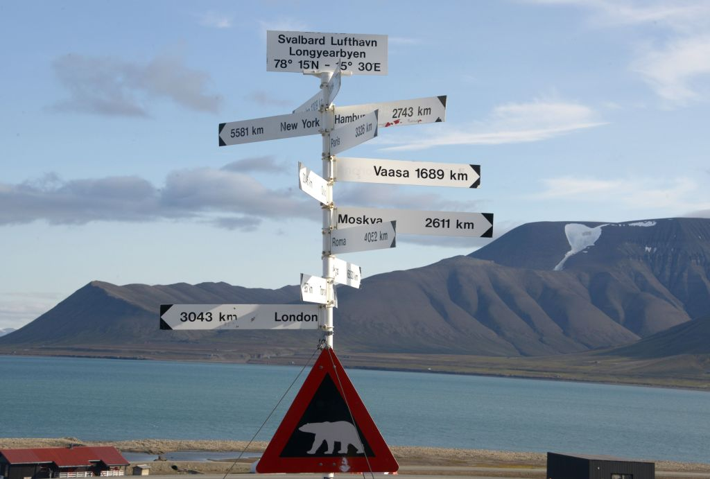 a signpost and a polar bear warning sign at the Longyearbyen airport.