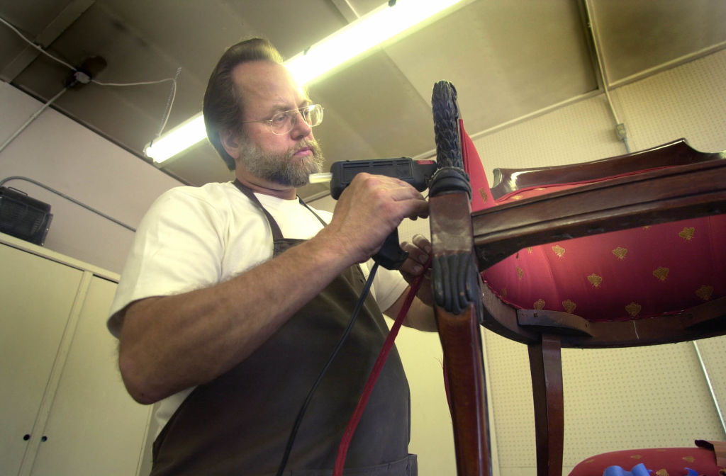 Man using a hot glue gun on a chair