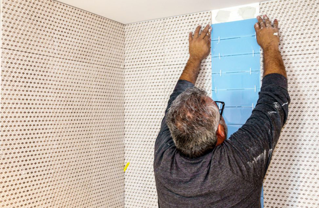 Man installing bathroom tile