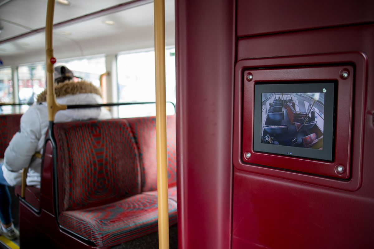 A monitor shows CCTV live feed on a double decker London bus.