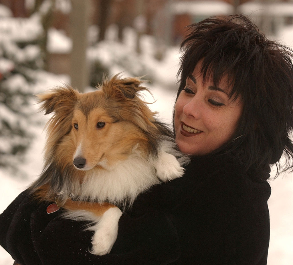 A woman holds and smiles at her sheltie.