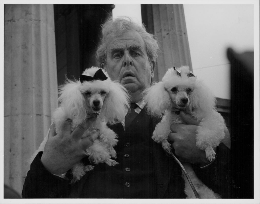 A man looks distraught as he holds a small poodle in each hand.