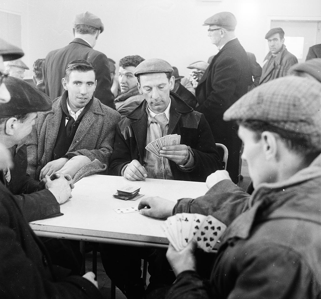 a group of men playing cards on the dock