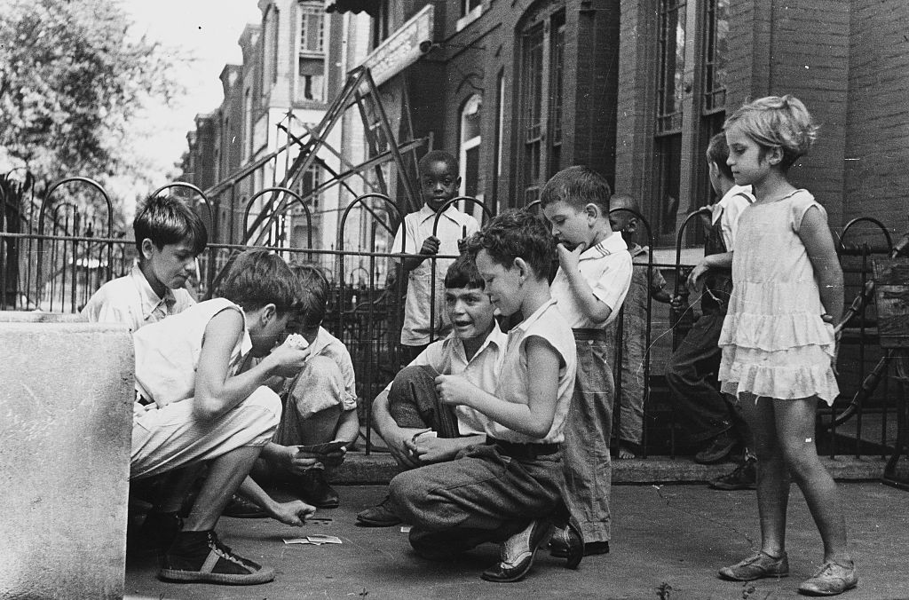 a group of kids playing cards on the street