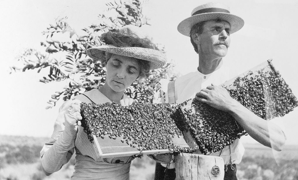 A black and white photo shows a beekeeping couple causually holding on to their beehives.