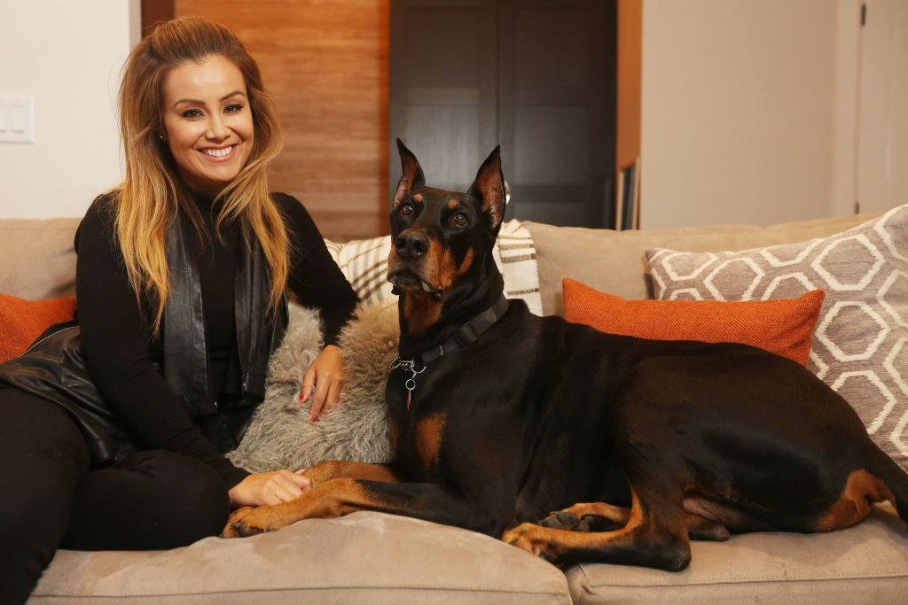 A woman sits next to her doberman and holds its paw.