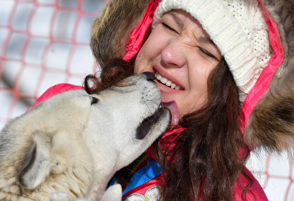 A woman squints while a dog licks her chin.