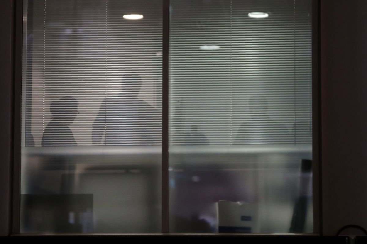 The silhouettes of people are seen through blinds inside the offices of Cambridge Analytica.