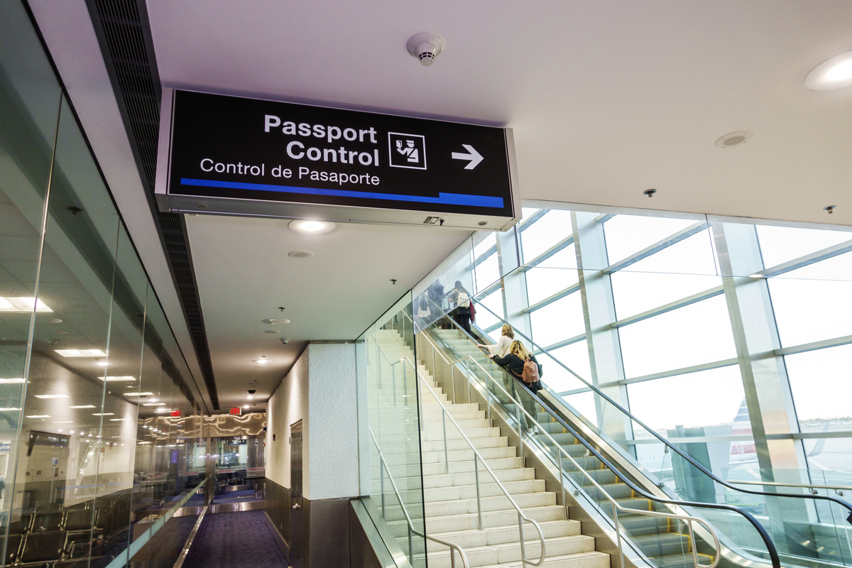 Bilingual passport control sign points to passport approval in a Miami International Airport.
