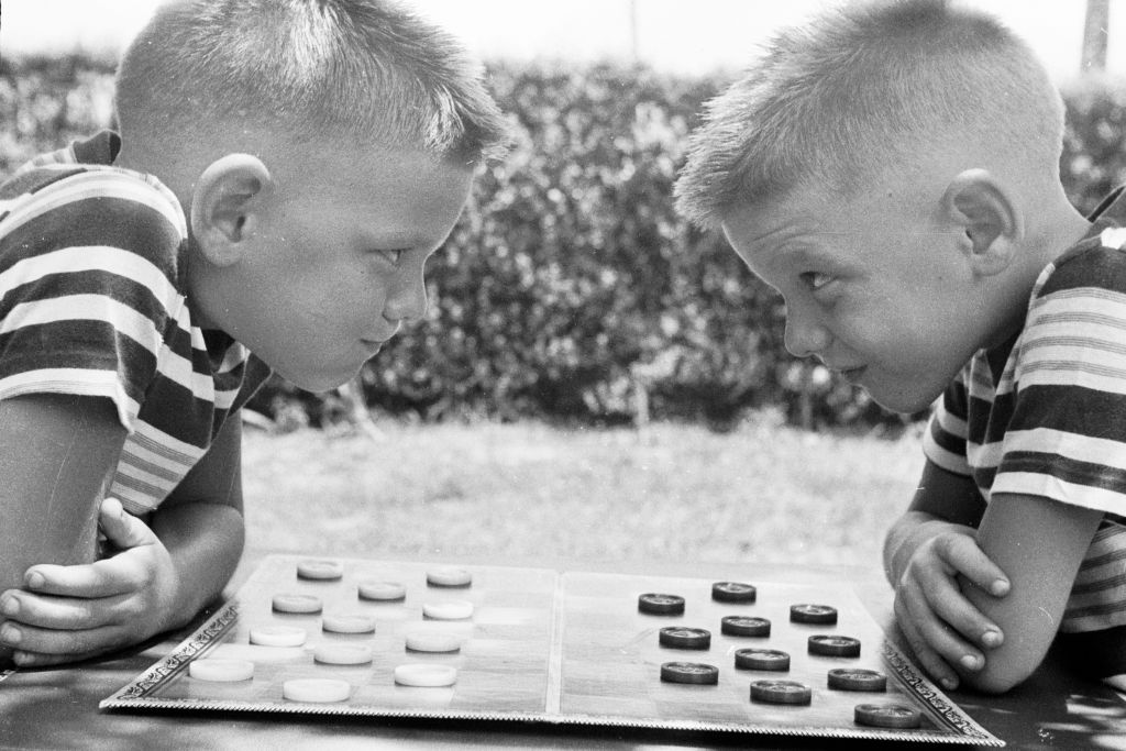 circa 1955: Identical twins Bobby and Jerry psych up for a game of checkers