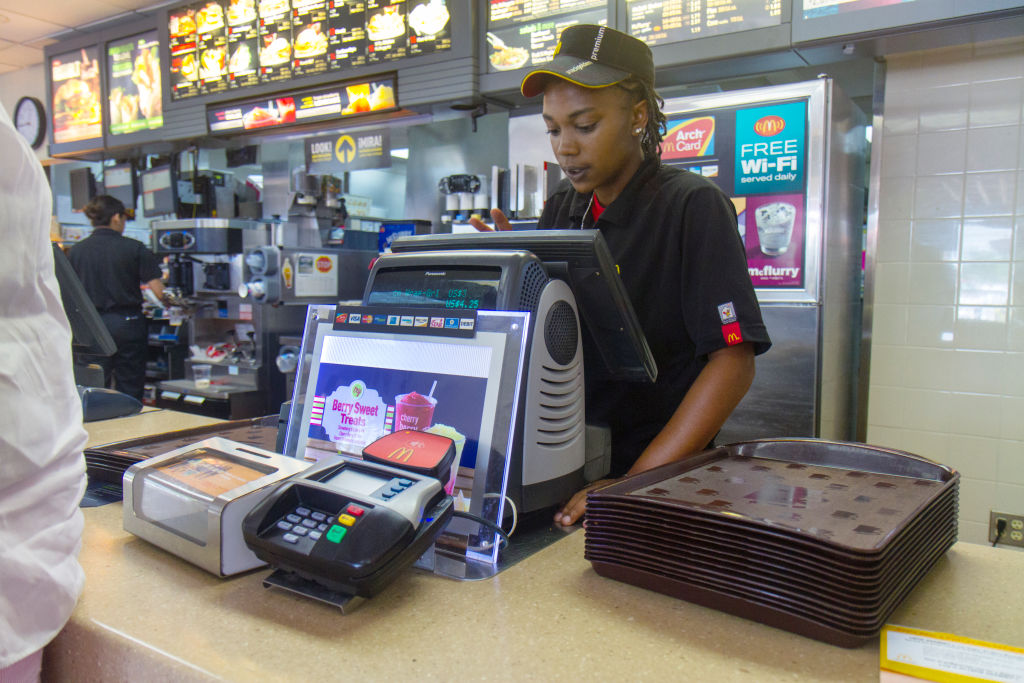 A cashier working behind the counter at McDonalds