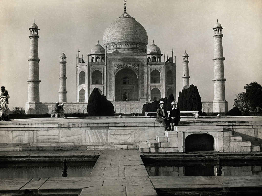 Agra, India: Couple seated at the Central Fountain of the Taj Mahal.
