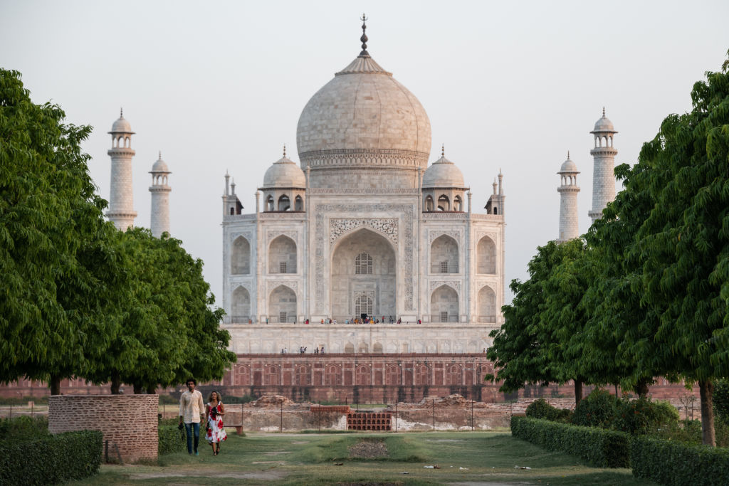 As the sun sets on 14 May 2019, a tourist couple walk in gardens near the Taj Mahal
