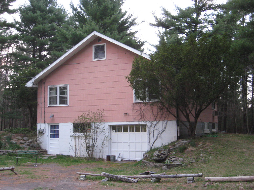 a house painted pink and white near several trees