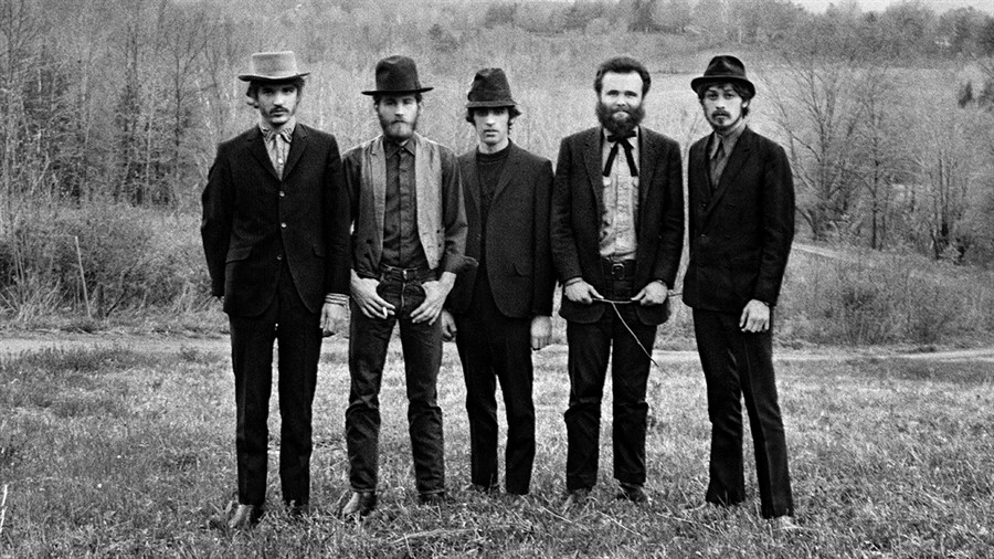five members of the band standing in a field