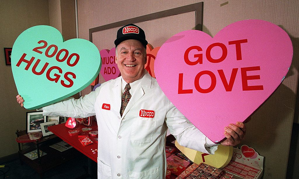 A man holds up two giant conversation hearts.