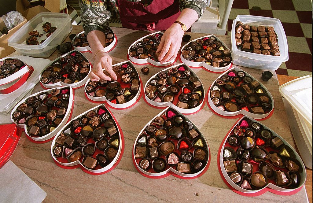 A worker places chocolates into heart-shaped boxes.