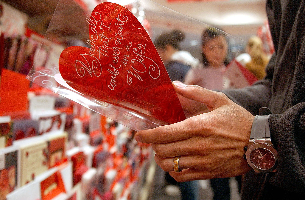 A man reads a Valentine's Day card in the card aisle of a store.