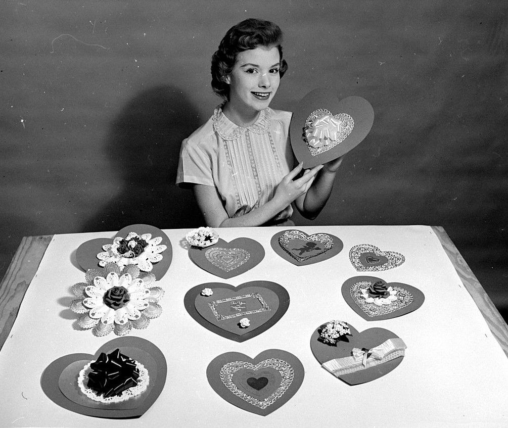 A woman makes heart-shaped cards.