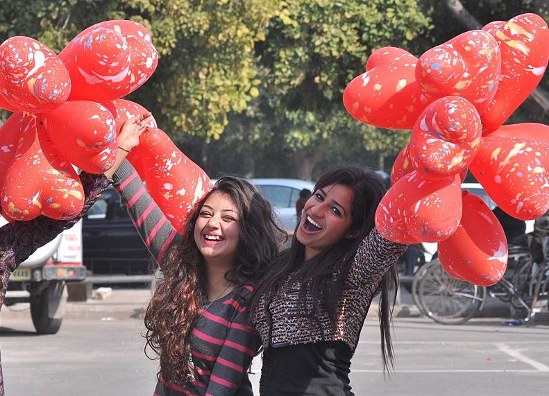 Two girls hold up heart-shaped balloons.