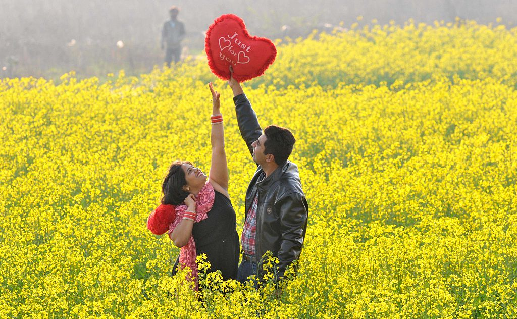 A young man teasingly holds a heart-shaped pillow out of his girlfriend's reach.