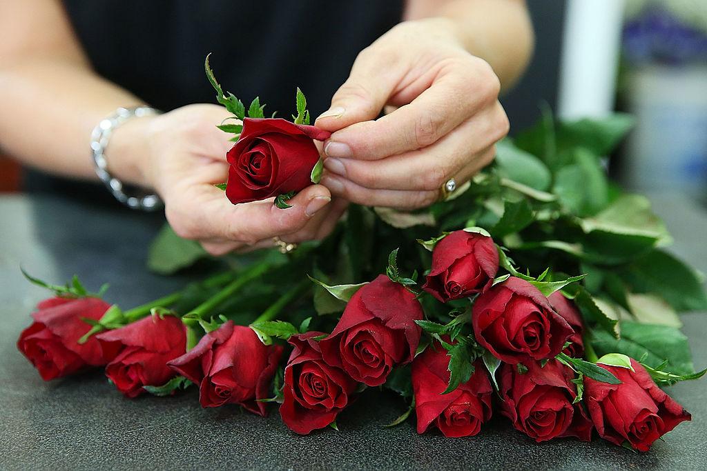 A florist prepares a dozen red roses.
