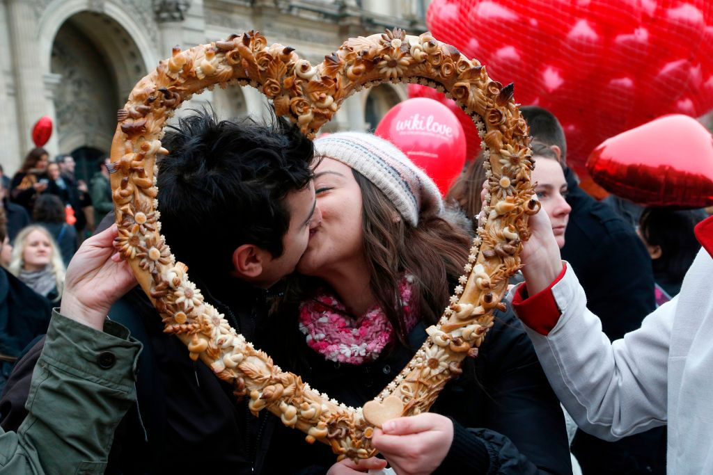 A couple kisses behind a heart wreath.