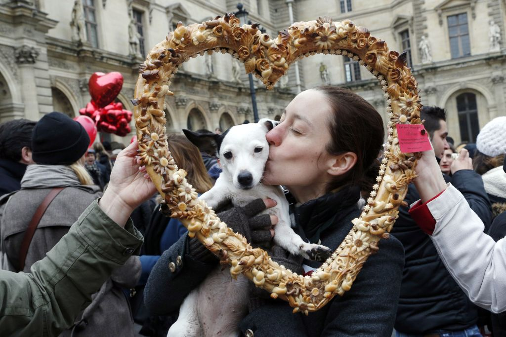 A woman kisses her dog behind a heart-shaped cutout.