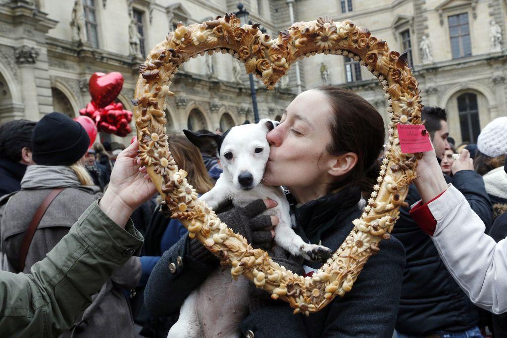 A woman kisses her dog behind a heart-shaped cutout.