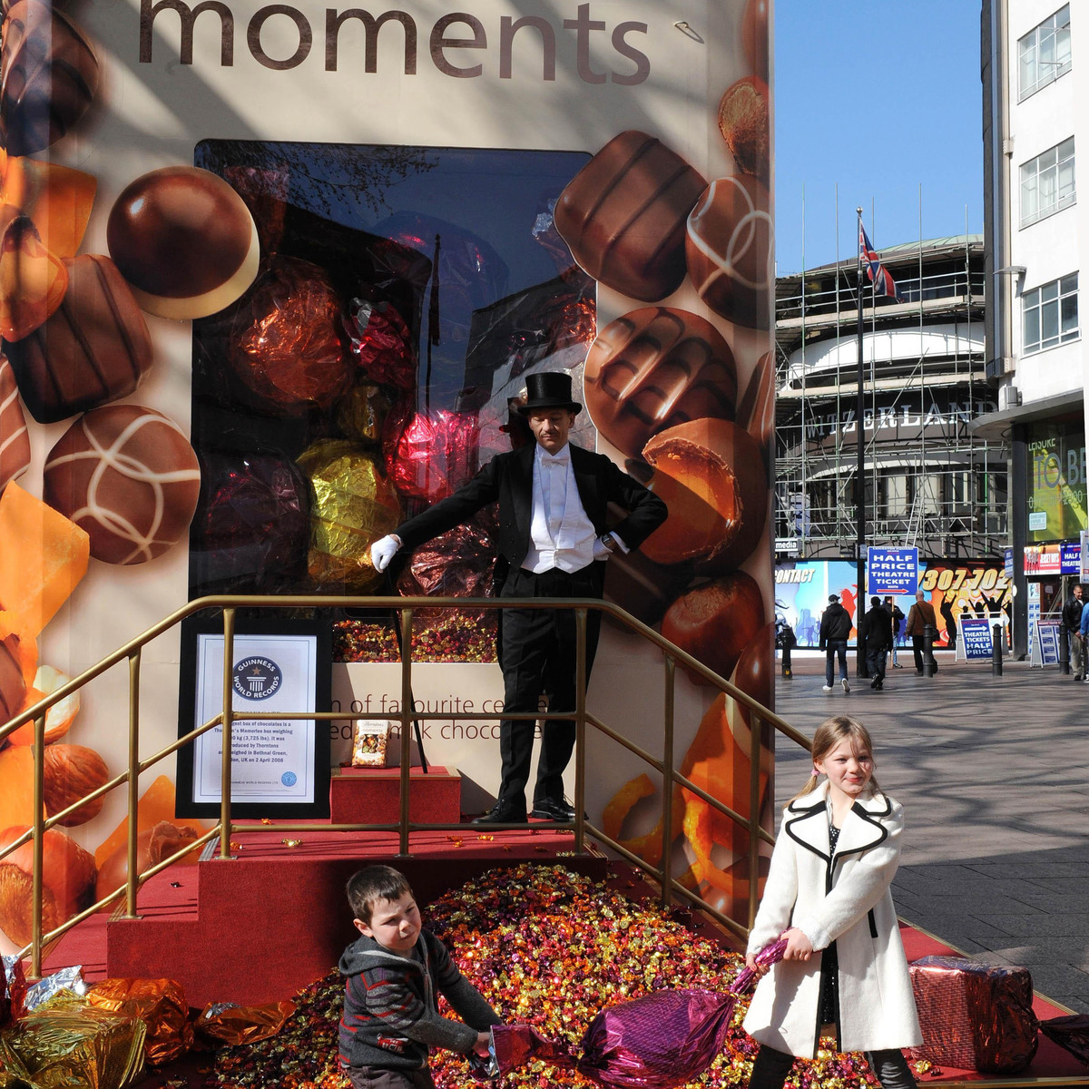 A man and two children stand in front of the largest box of chocolates.