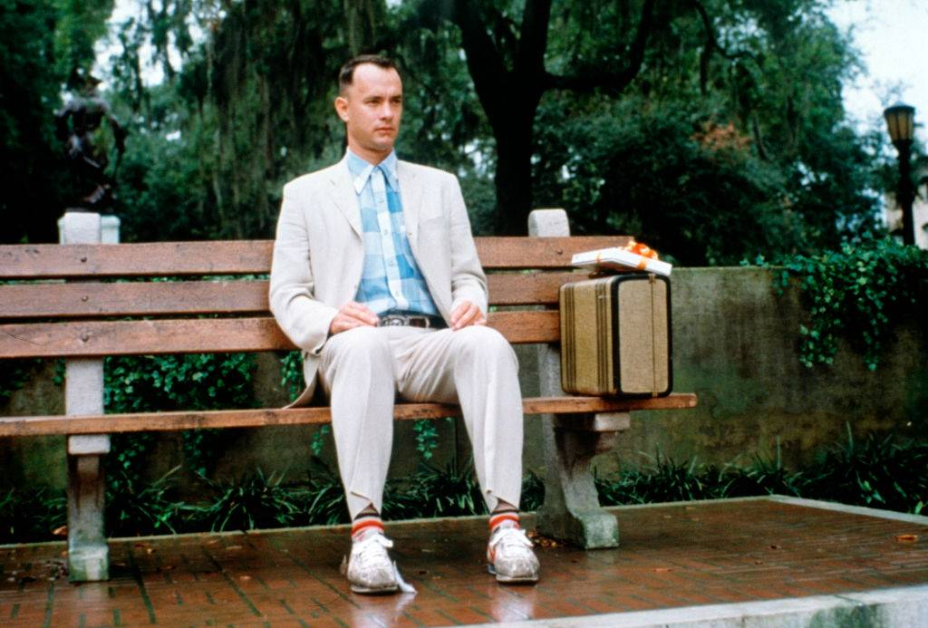 tom hanks sitting on a bench in forrest gump with a suitcase and a box of chocolates