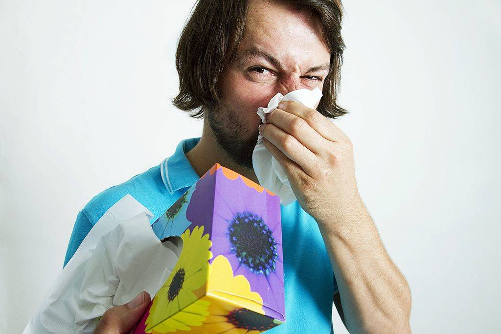 a man holding a tissue box and blowing his nose