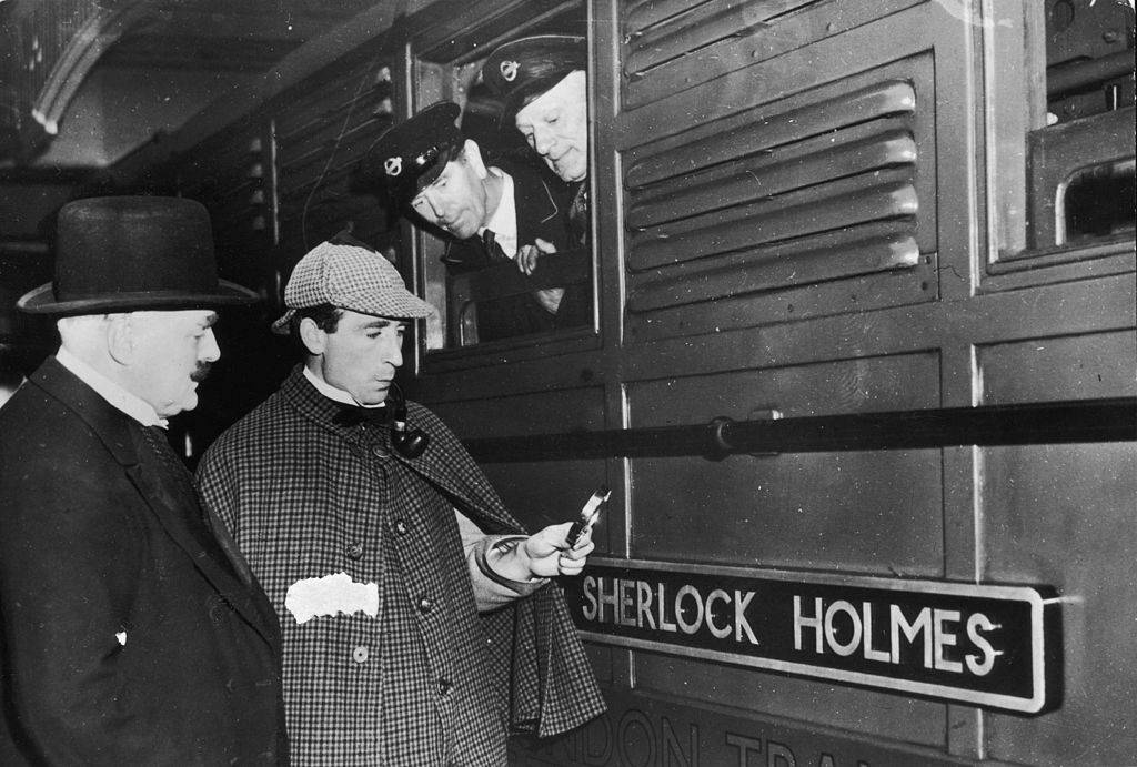 sherlock holmes holding a magnifying glass at a train