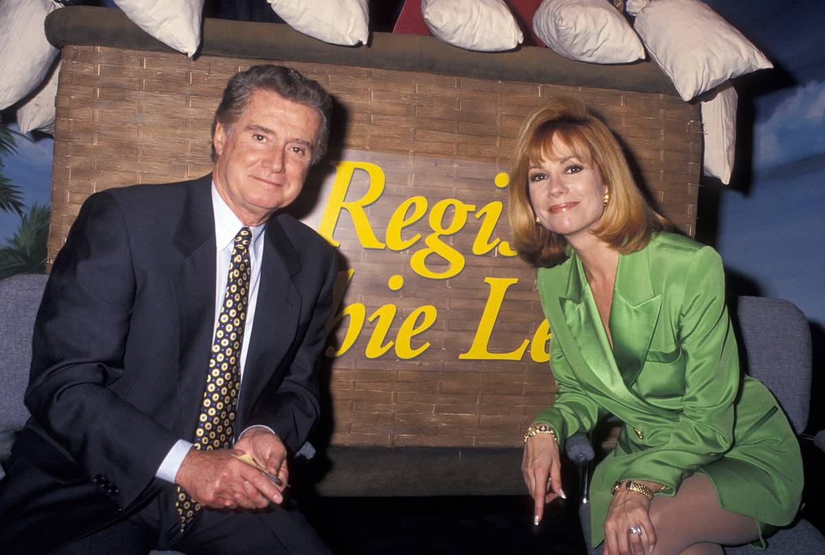 Regis Philbin and Kathie Lee Gifford pose in front of a sign.