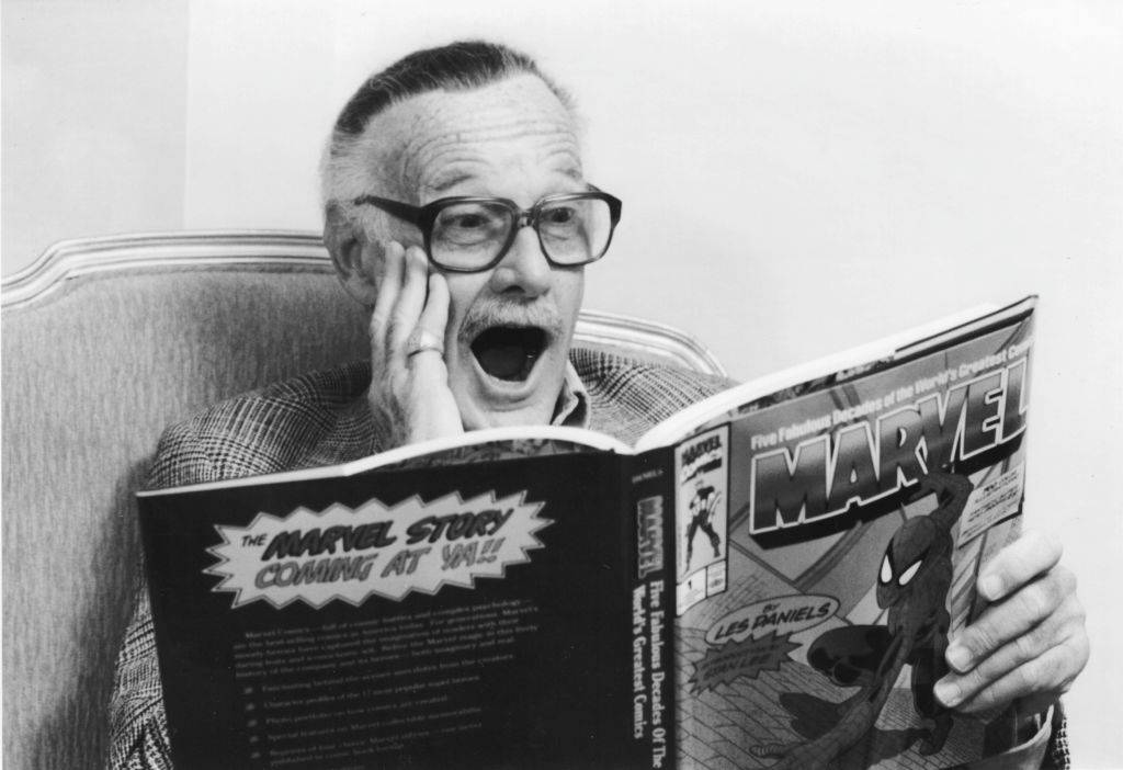 Comic book creator Stan Lee smiles while reading a book