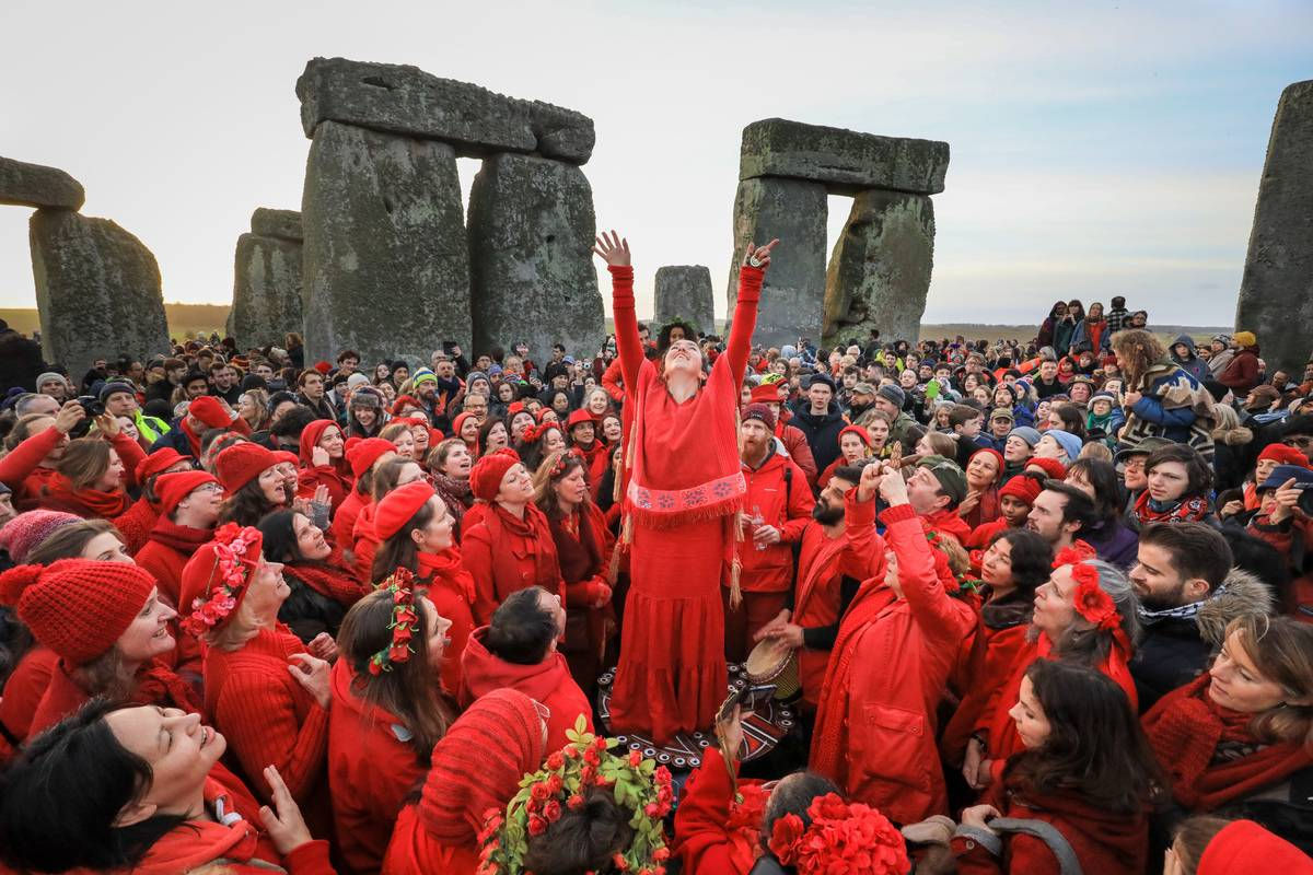 Members of the Shakti Sings choir sing as druids, pagans and revellers gather in the centre of Stonehenge.