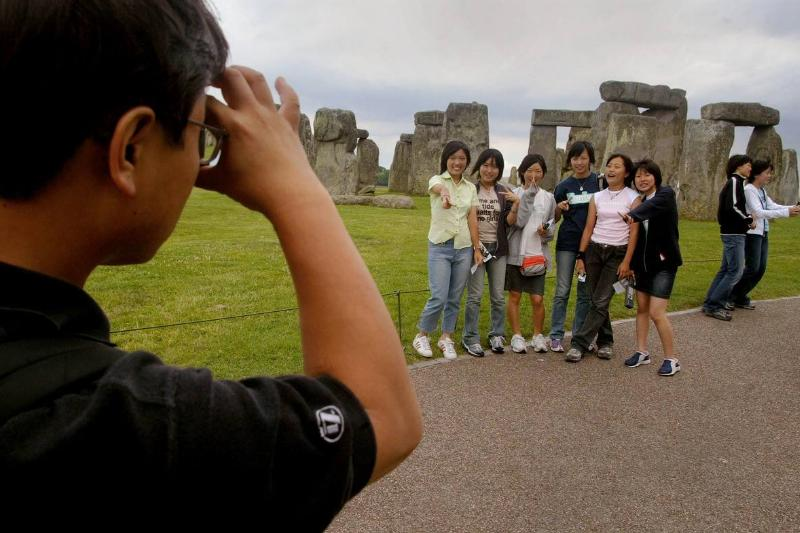 Tourists pose for a photograph outside of Stonehenge.