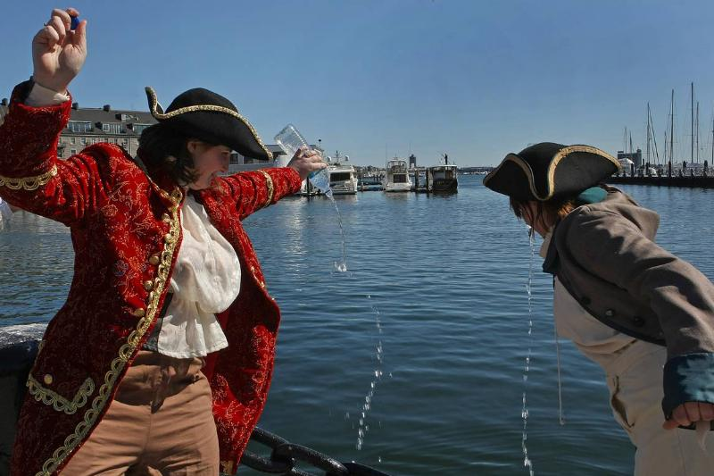 Boston Tea Party re-enacters pour water into the harbor.