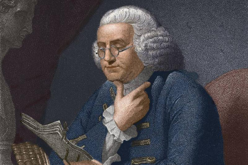 An illustration shows Benjamin Franklin reading at a table.