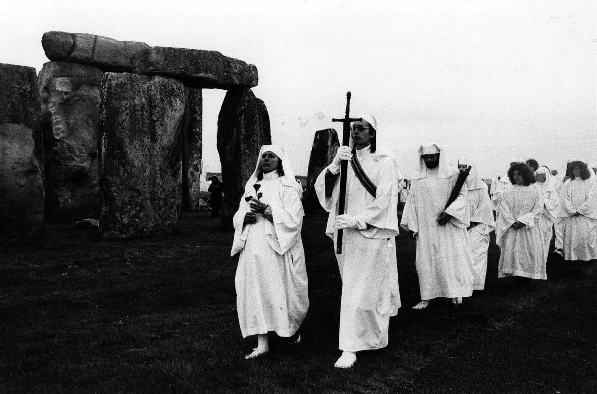 In 1978, a procession of Druids walks by Stonehenge.