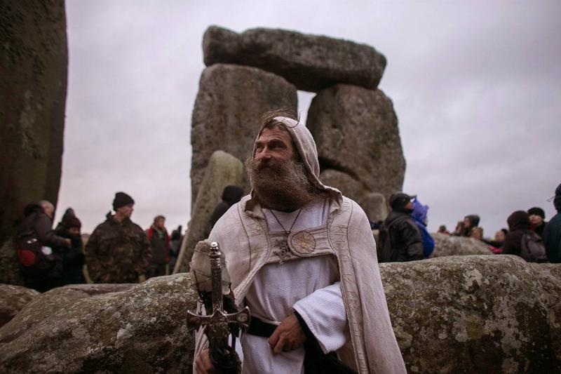 A Druid man poses in front of Stonehenge.