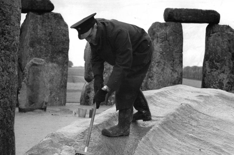 An officer scrubs the stones in Stonehenge.