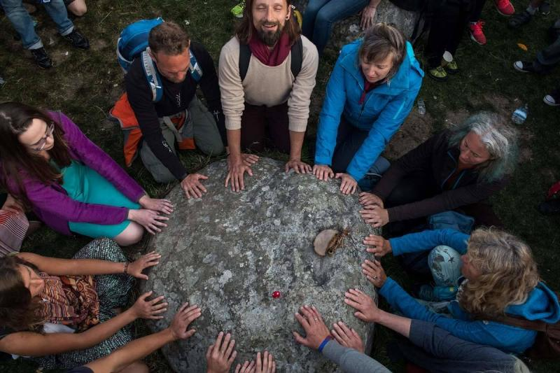 Revellers touch a stone and chant in a circle as they celebrate the Summer Solstice at Stonehenge.