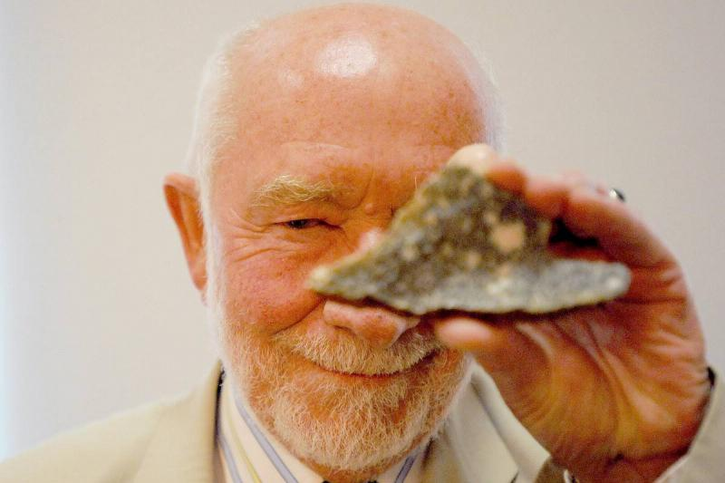 A professor holds up a piece of bluestone that was used for Stonehenge.