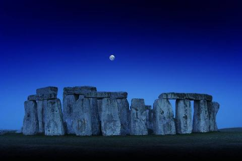 Stonehenge is pictured with the full moon in the sky.