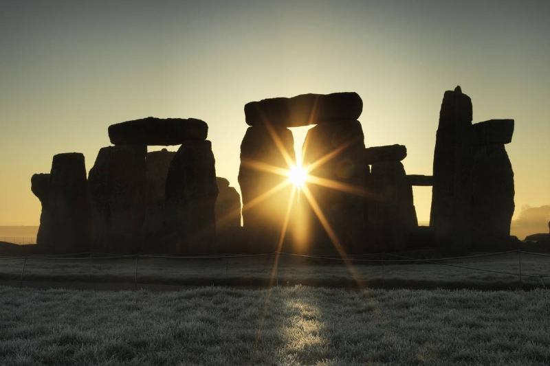 The sun shines through a trilithon during the winter solstice in Stonehenge.