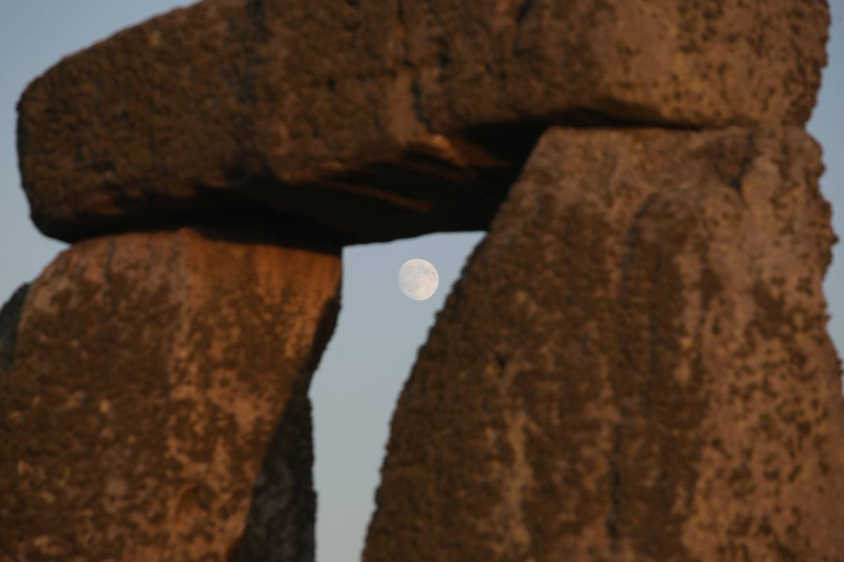 The full moon peers through a Stonehenge monument.