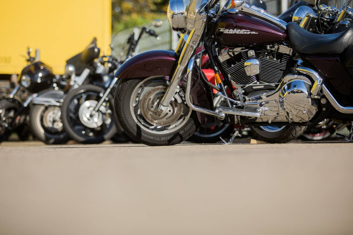 Harley Davidsons are parked in a row.
