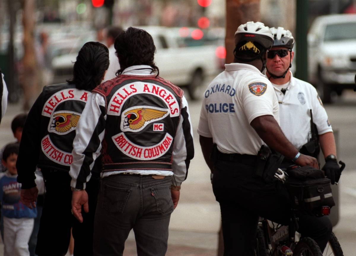 Hells Angels walks by police officers.