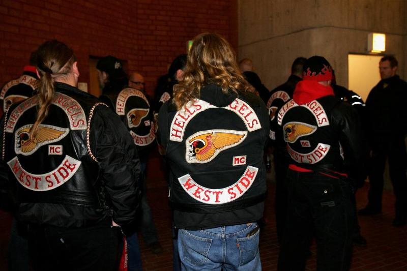 A group of Hells Angels members gather outside of a building.